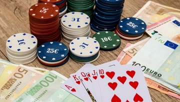playing cards on the table with EU chips and cash bills